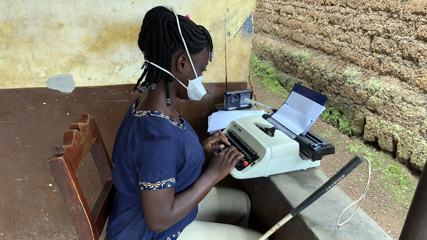 A girl with a face mask sits outside listening to a radio.