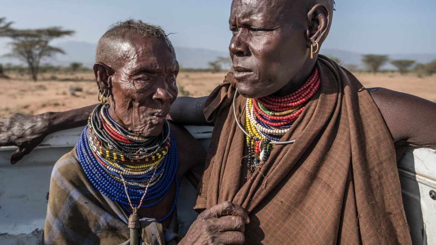 Two trachoma patients wearing traditional clothing standing next to a vehicle in a landscape in Kenya.