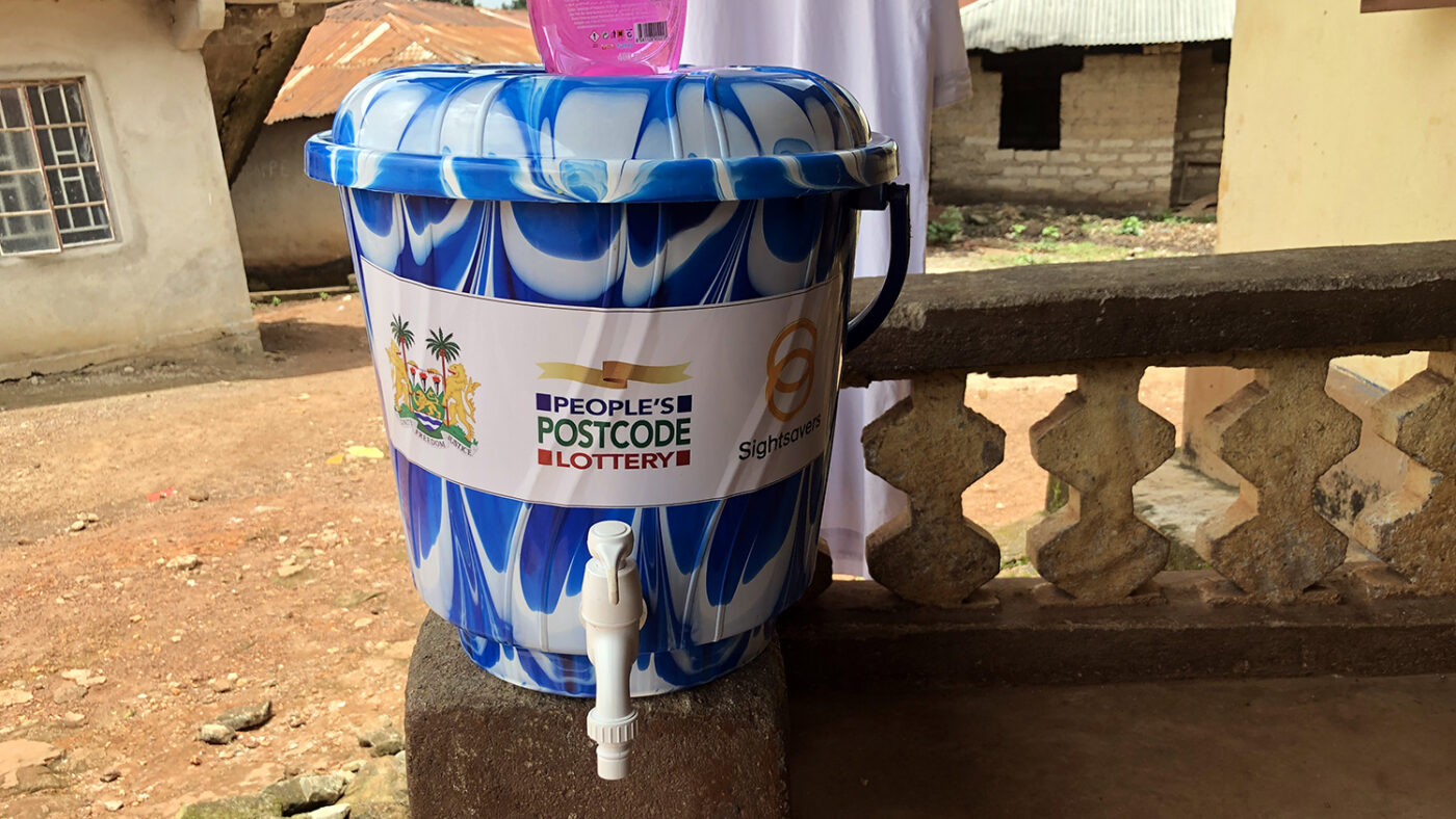 A water bucket with Sightsavers and People's Postcode Lottery logos on the front.