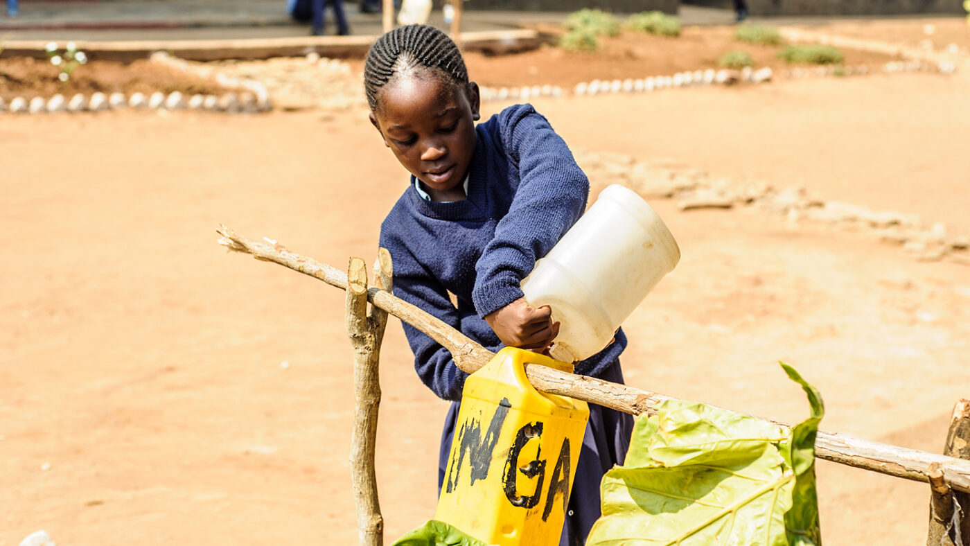 A young girl fills a tippy tap with water.