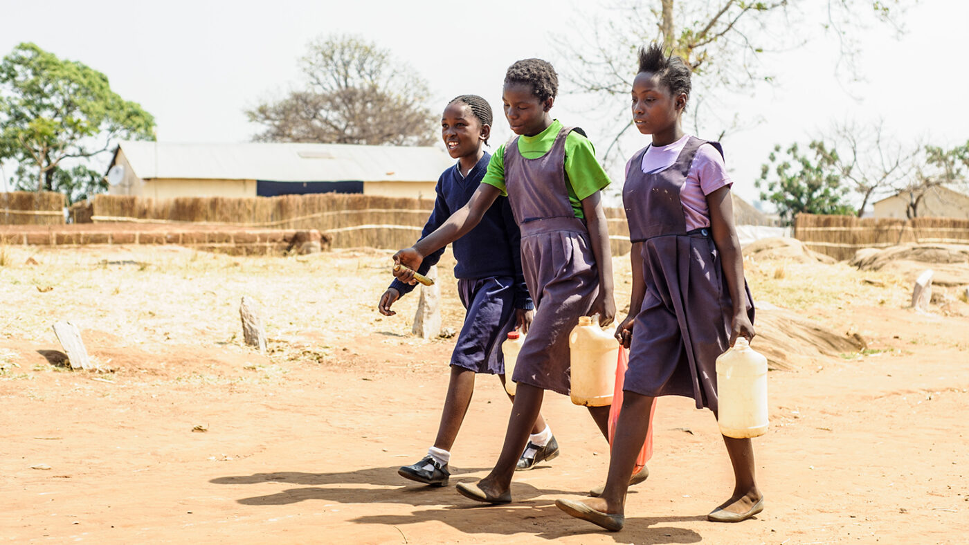 Three students carry clean water to school.