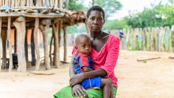 A mother sitting down, holding her child who is sat on her lap.