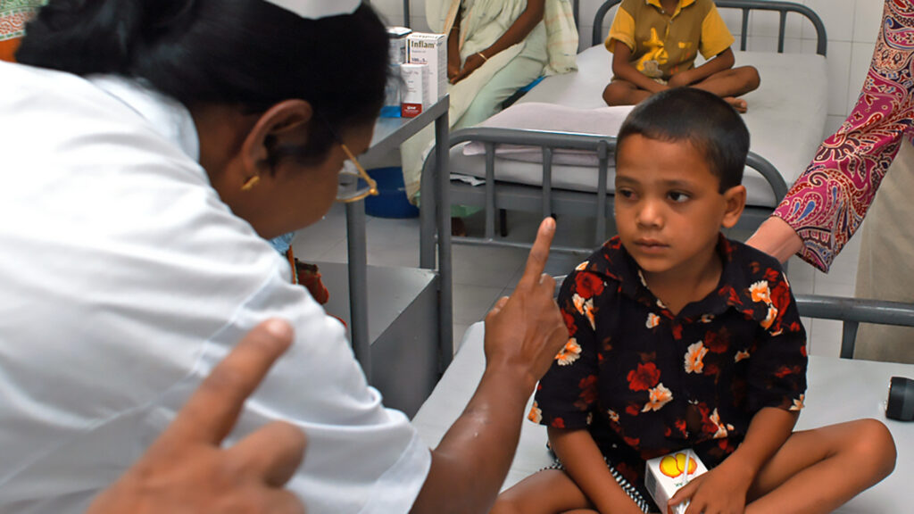 A young boy sits on a hospital bed, looking at a nurse with a finger held up.