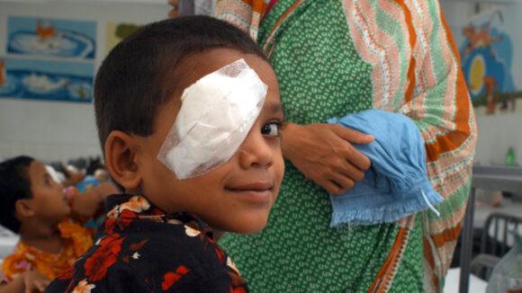 Young boy with bandage over one eye.
