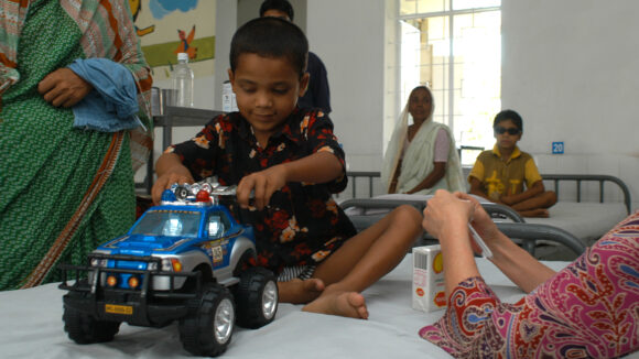 A boy sitting on a hospital bed, playing with a toy truck.