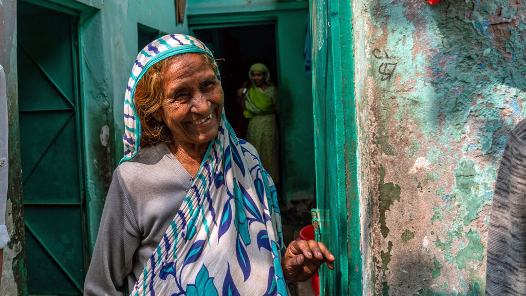 A smiling women stands in a doorway.