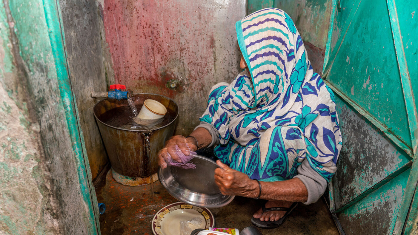 A woman sits on the ground washing dishes.