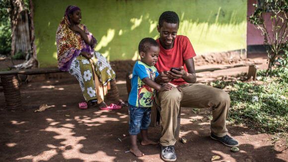 A young boy looks at his father's phone.