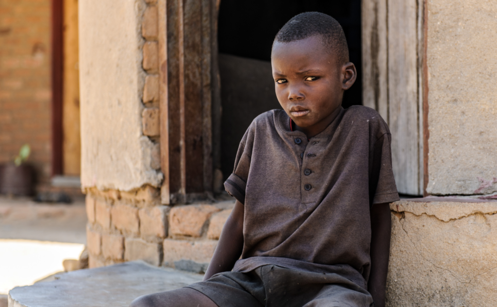 A young boy, Bretty, looks at the camera while sat on the ground outside a doorway.