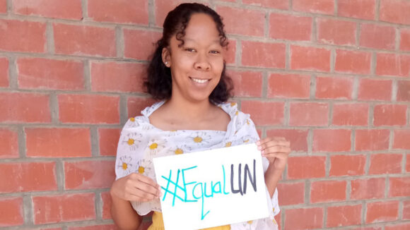 A woman standing by a brick wall holds a sign reading #EqualUN.