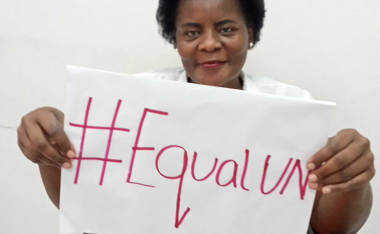 Eufémia Amela smiles and holds a sign saying #EqualUN.