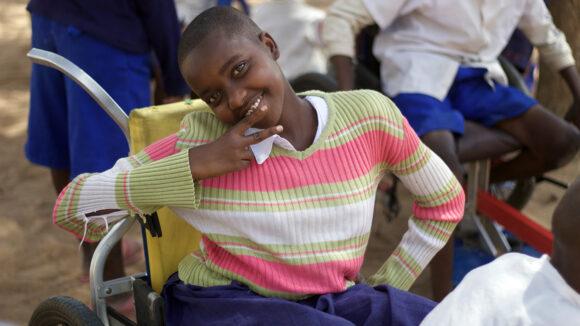 A girl in a wheelchair smiles to camera.