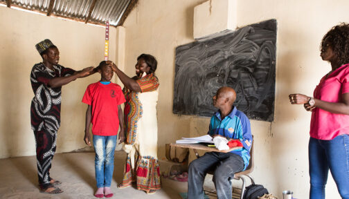A school-aged boy has his height measured to receive deworming treatment during a school based mass drug administration.