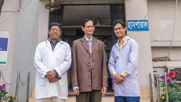 Three men stand outside a hospital entrance.