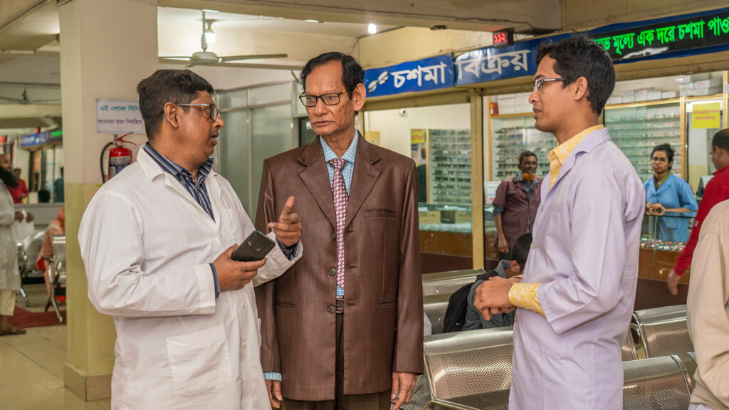 Three men talking in the lobby of a hospital.
