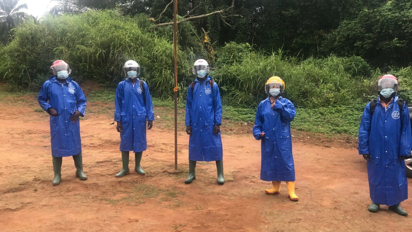 Five people dressed in protective clothing stand outside.