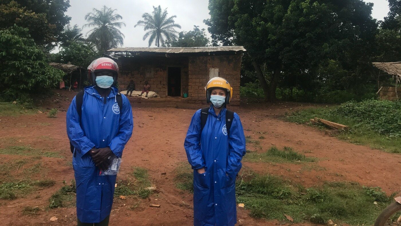 Two people standing outside in protective clothing.