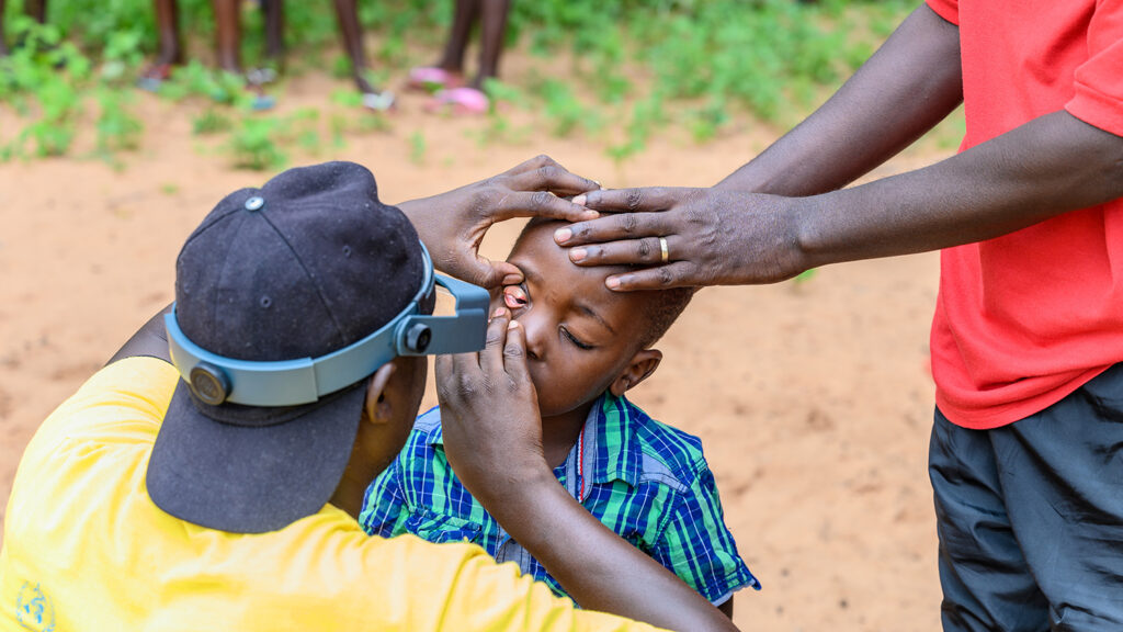 A medical nurse examines a child's eye while another adult puts a supportive hand on the child's head.
