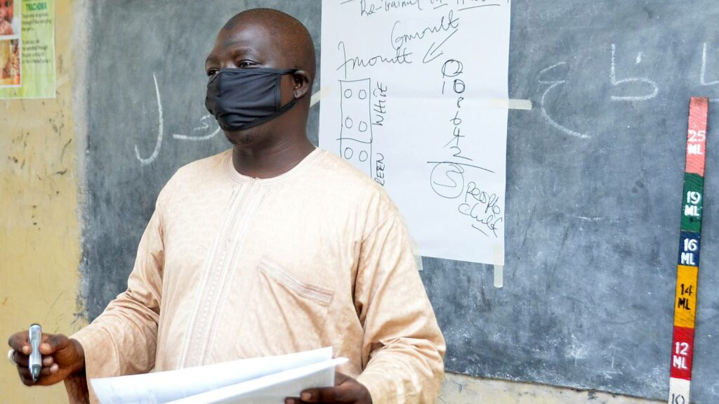 A man wearing a protective mask presents in front of a blackboard next to a dose poleivers training to antibiotics distributers in a classroom at Government Day Secondary School, Jigawa State