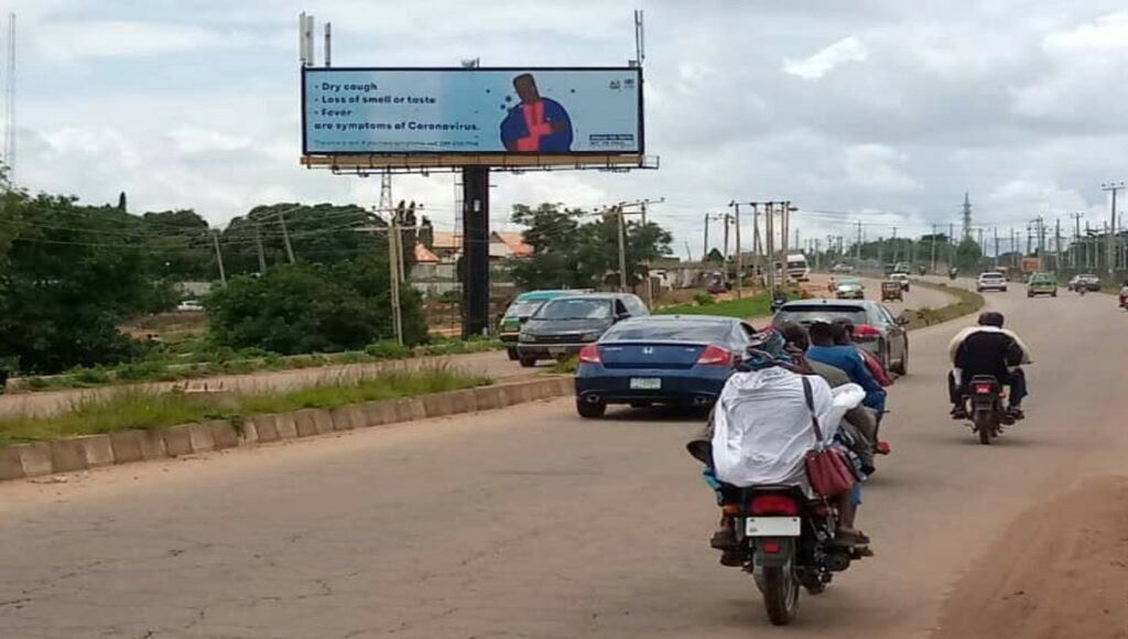 A billboard with COVID-19 messaging on it can be seen at the side of a road with cars a bikes going along it.