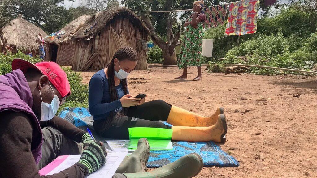 A woman an a man sit outside, recording data.