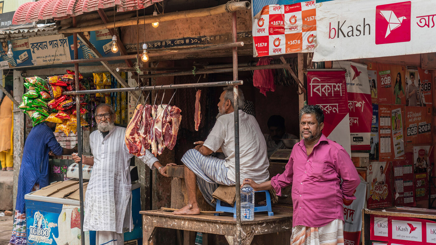 Men standing next to a raw meat stand.