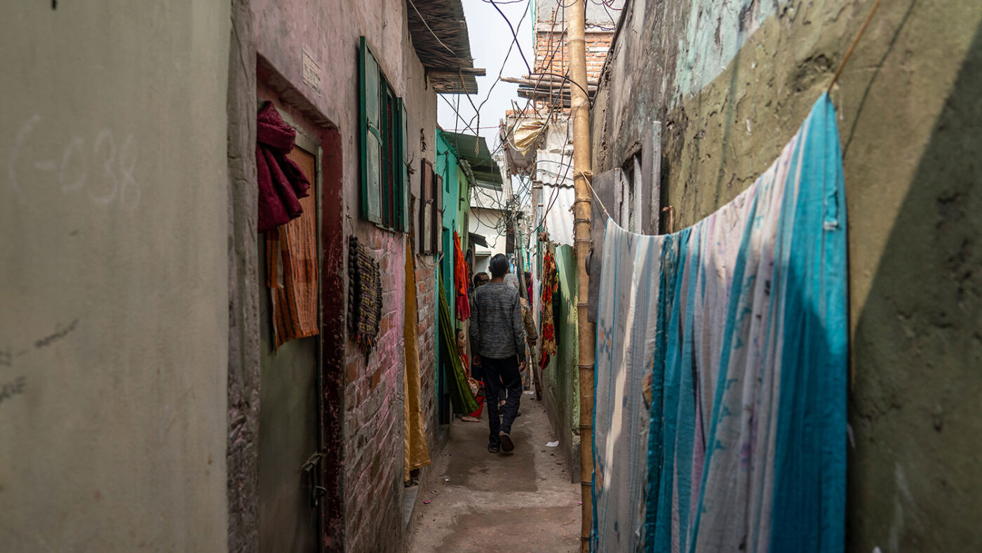 A slim walkway through an informal urban settlement.