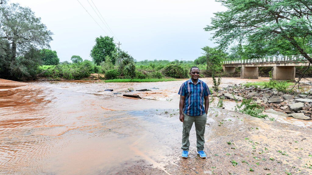 Senior programmes lead in Zimbabwe, Peter Bare, stands next to a flooded road.