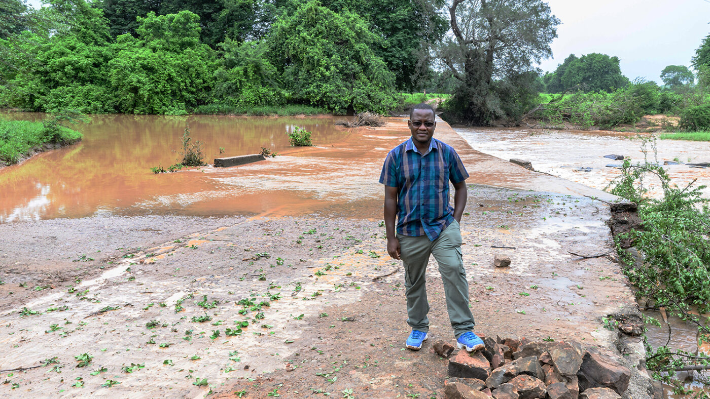 Senior programmes lead in Zimbabwe, Peter Bare, stands in front of a flooded road.