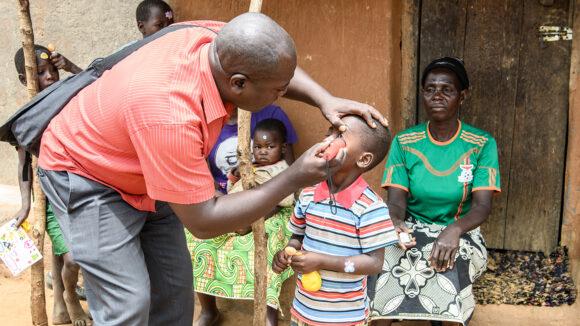 Man examining a child's eye.