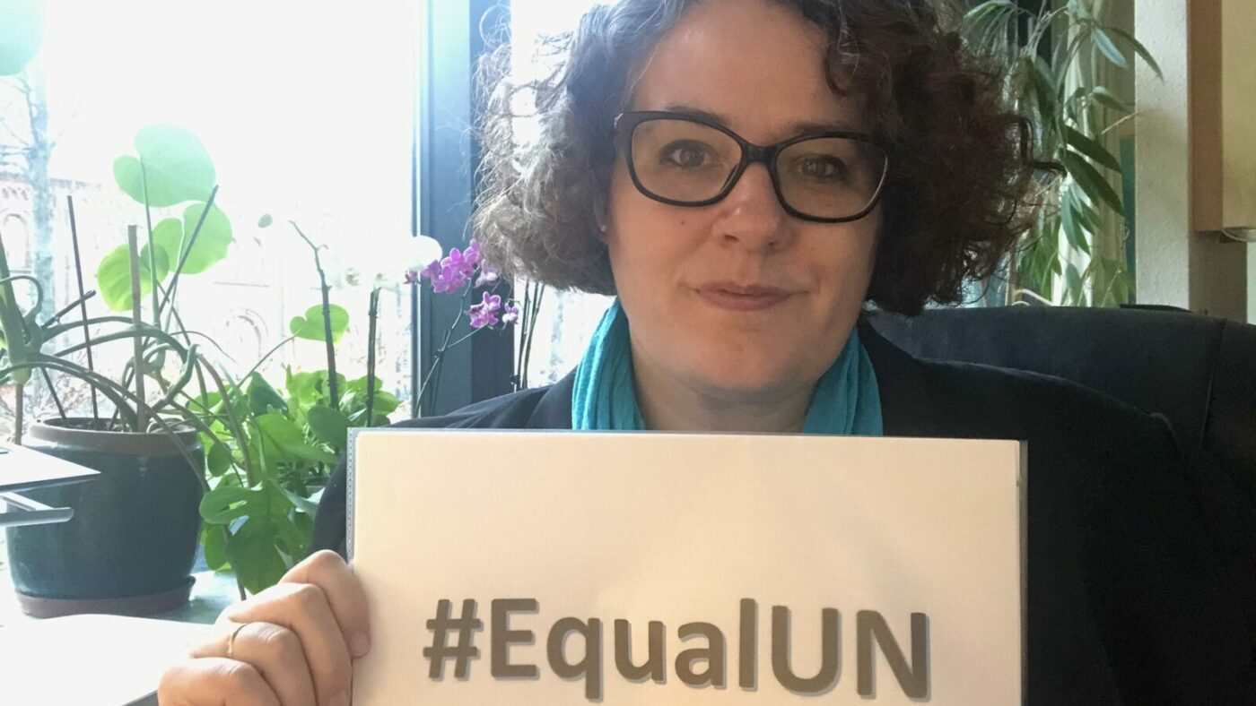 A woman holds a sign saying #EqualUN.
