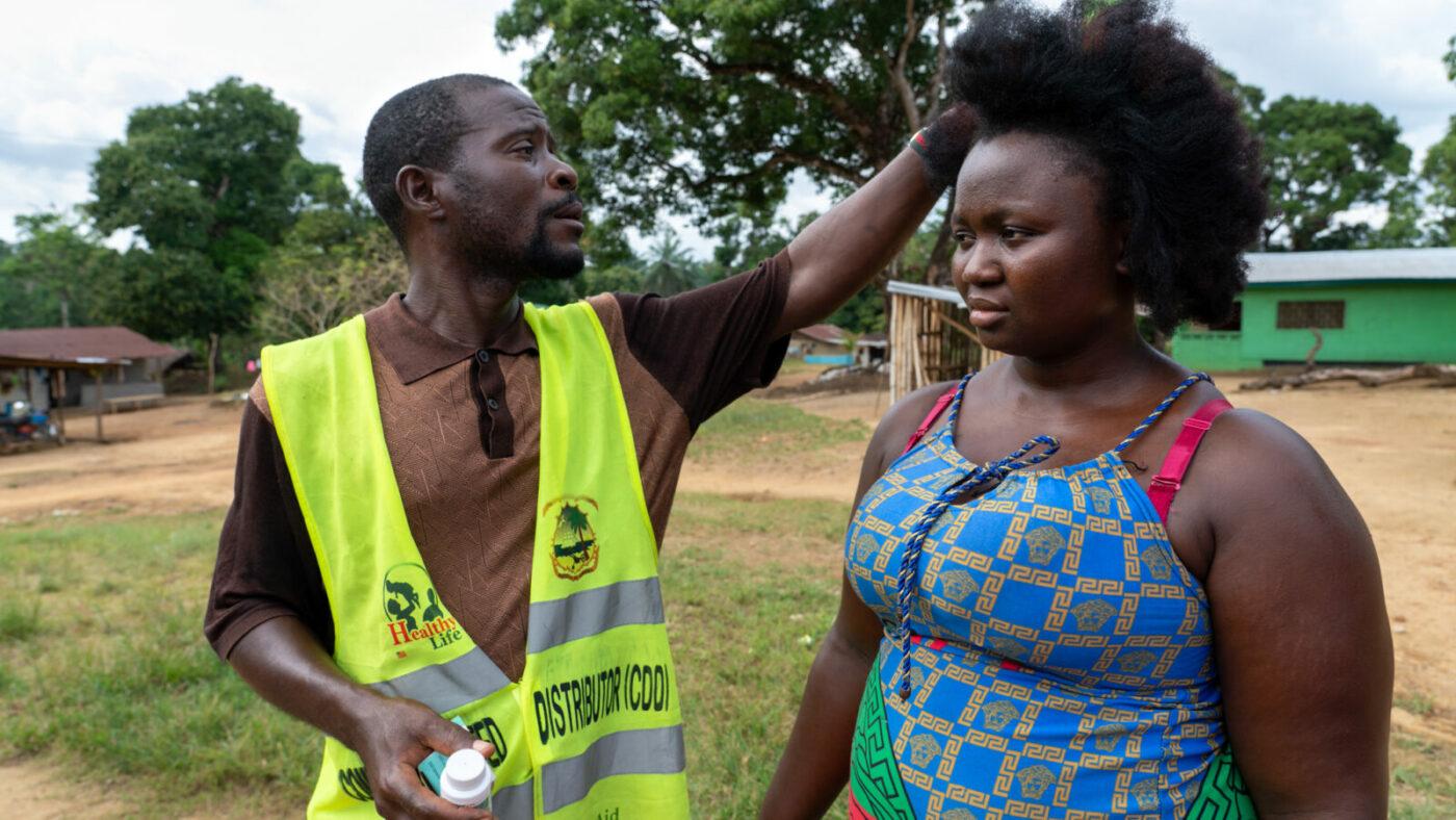 A community volunteer measures Jumah's height.