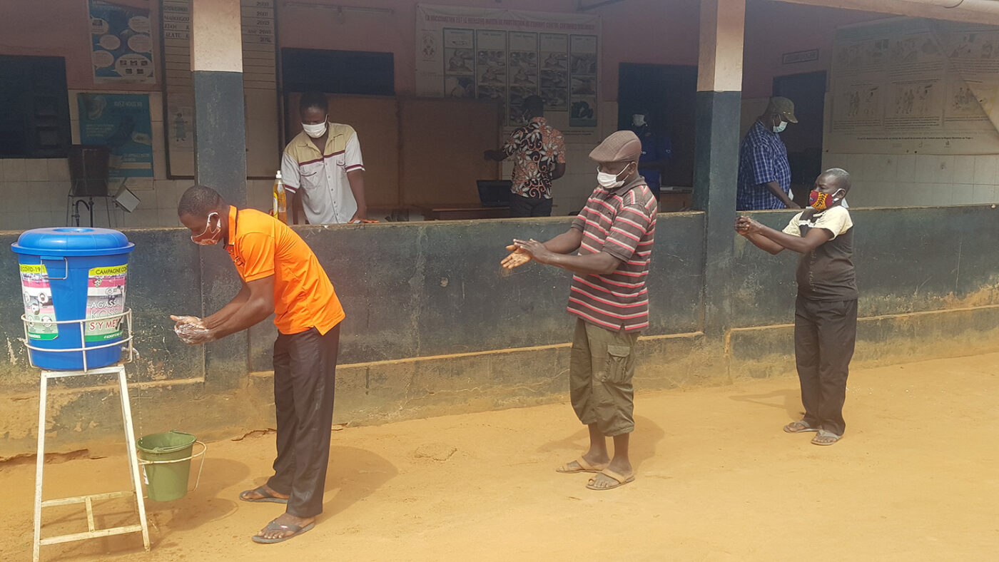 Volunteers wash their hands and practice social distancing before a training.
