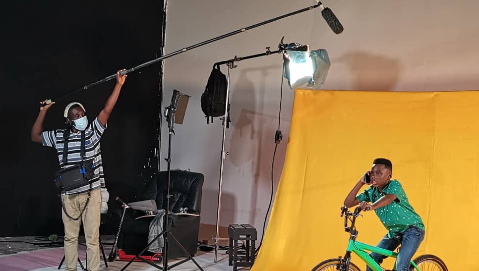 Behind the scenes at the recording of Ghana's social video. A man wearing a face covering holds a mic above a young boy who is sitting on a bike, on his phone in front of a yellow backdrop.