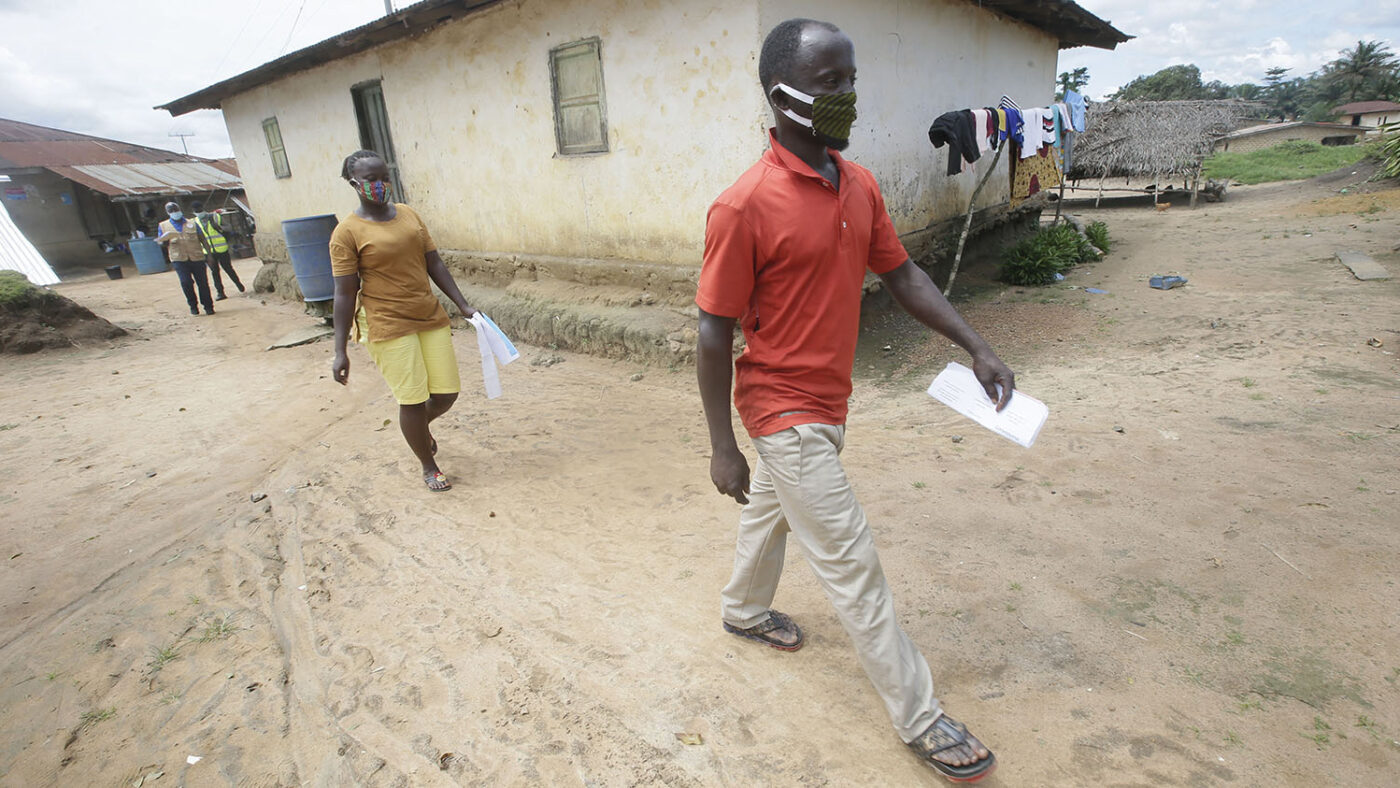 Two community volunteers, male and female, walk through the community.
