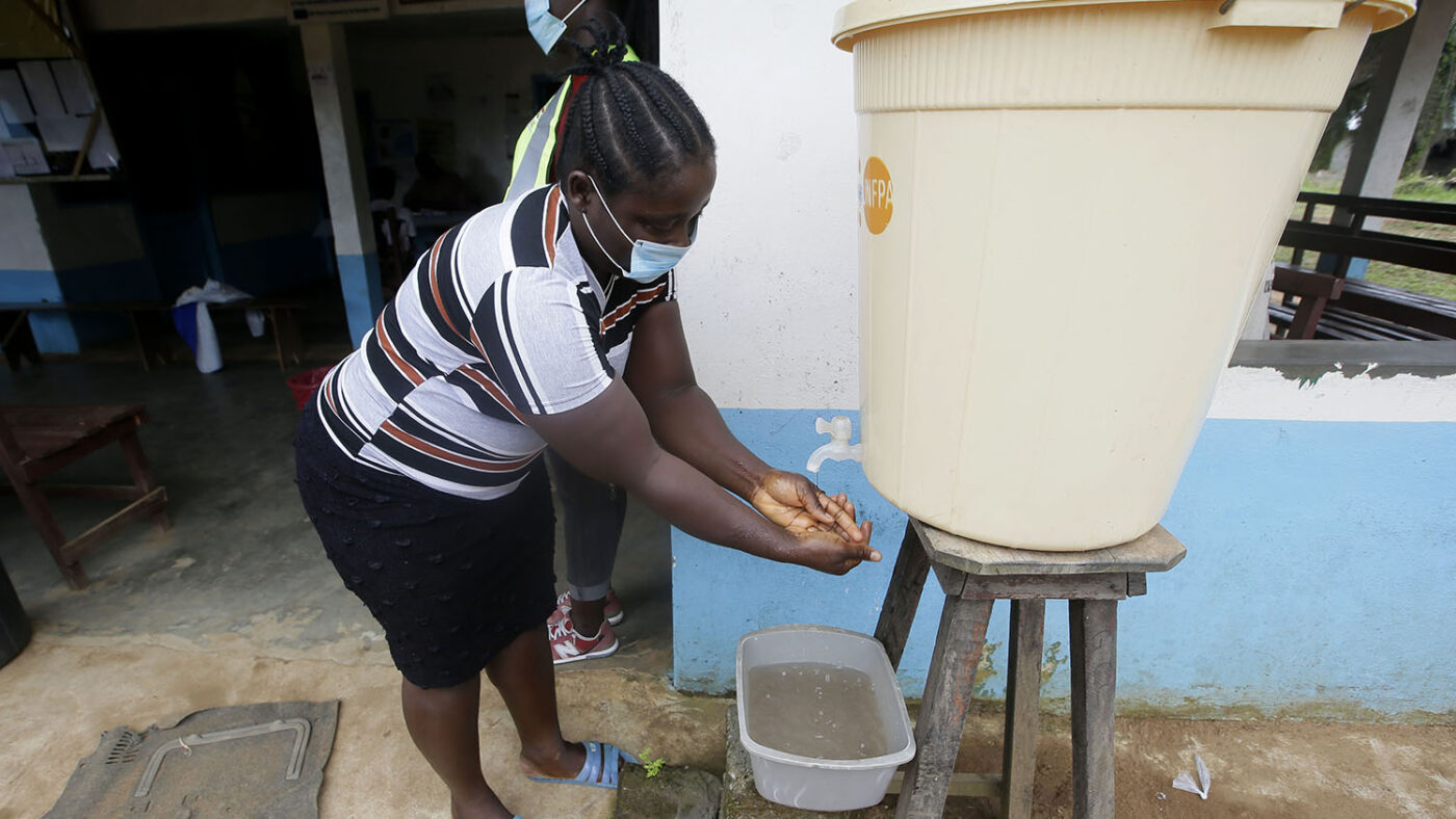 A woman wearing a mask washes her hands.