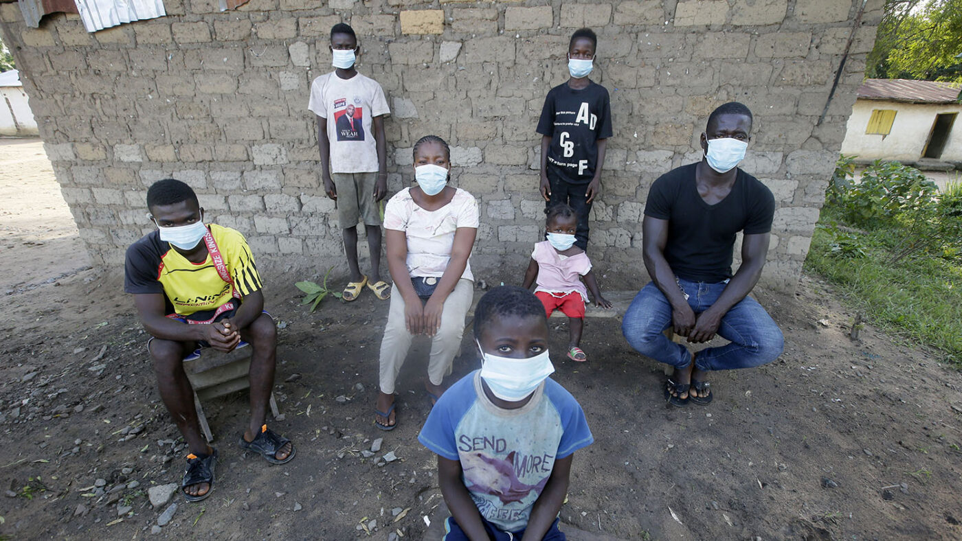 A family, all wearing masks, sit for a social distanced portrait outside their home.