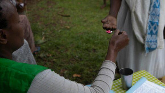 Woman gives man tablets on a teaspoon