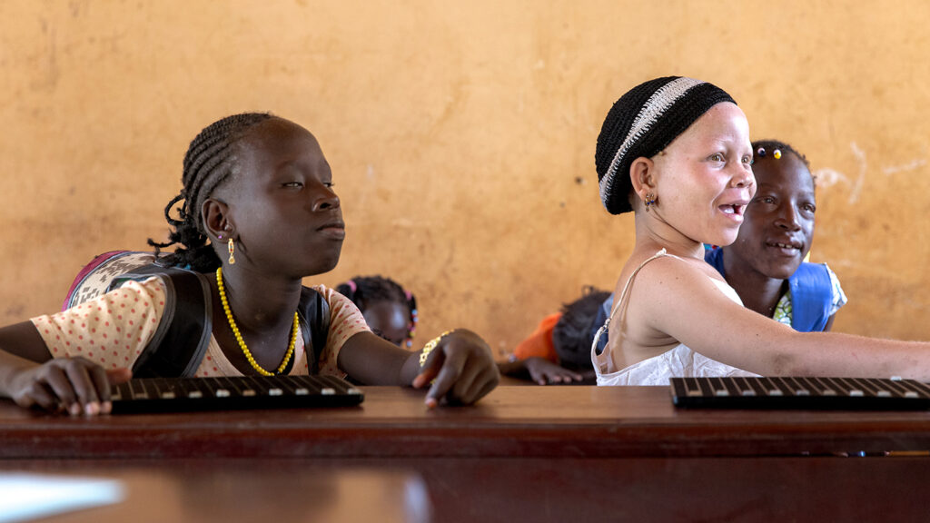 Two girls with visual impairments in a school.