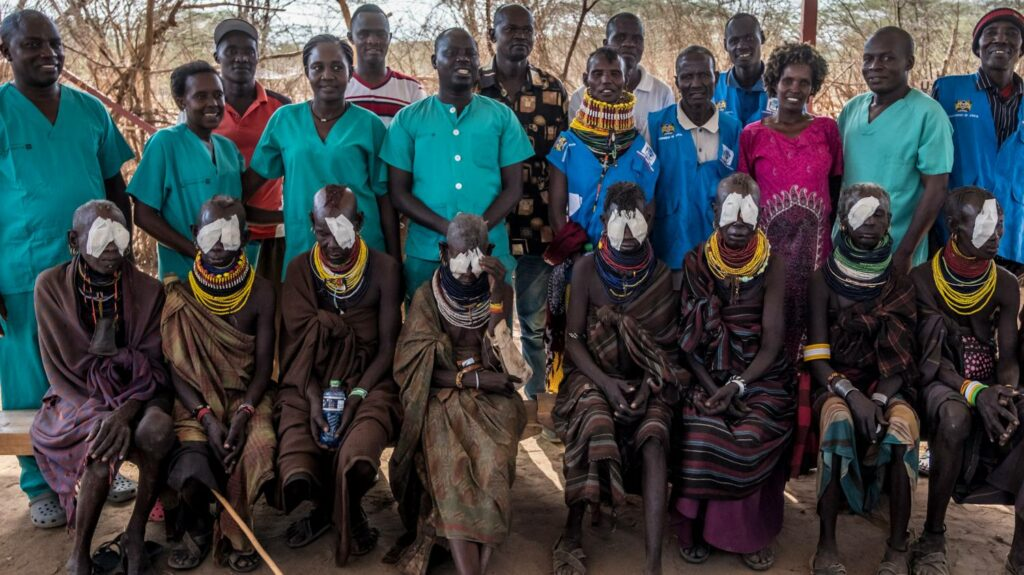 Surgeons and surgery patients wearing bandages over their eyes line up for a photograph