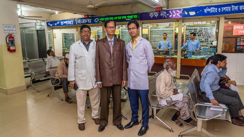 Three men stand in a waiting room in a hospital.
