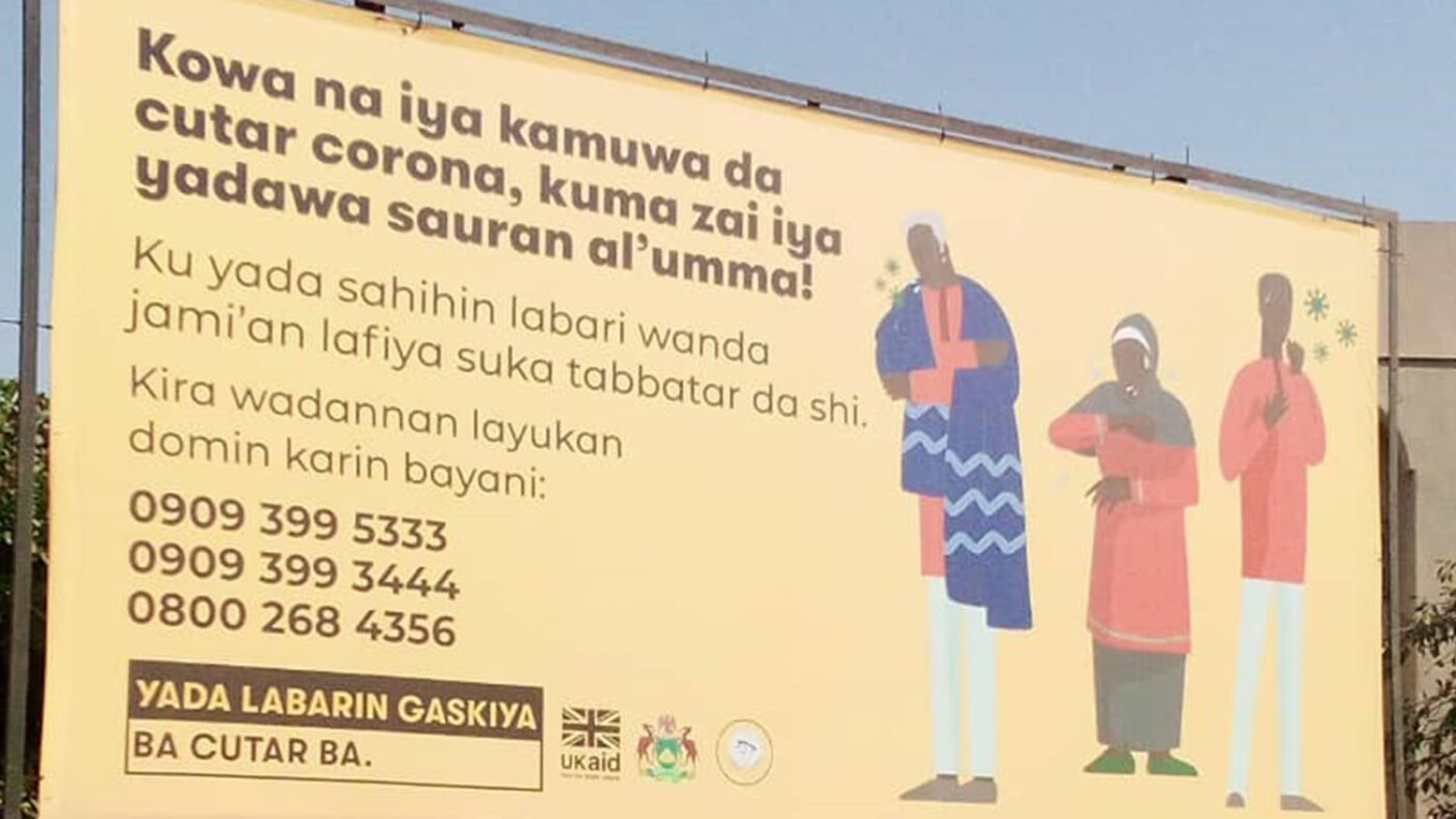 A billboard with COVID-19 messaging on it in local Nigerian language.