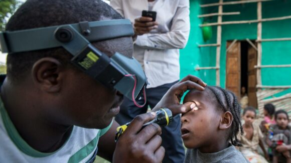 A man wearing magnifying glasses over his eyes shines a torch into a toddler's eye during a trachoma survey.