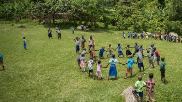 A group of children stand in a ring, while other children play around them on a grassy plain.