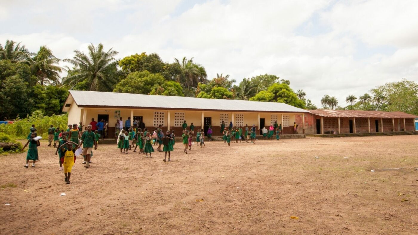 Children play on a playing field in front of a long, low school building