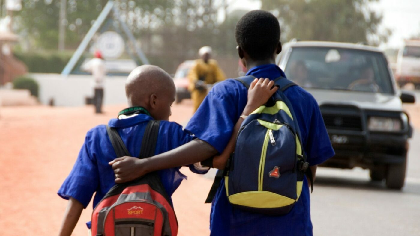 Two schoolboys, arm in arm, walk down a dirt track by the side of a road.