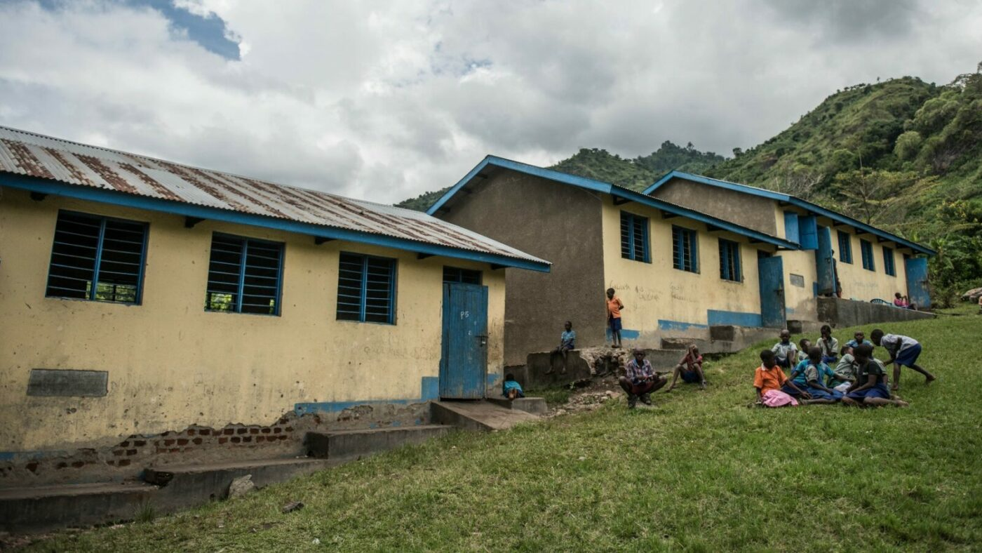Children play in front of a long, low school building, with lush green hills in the background.