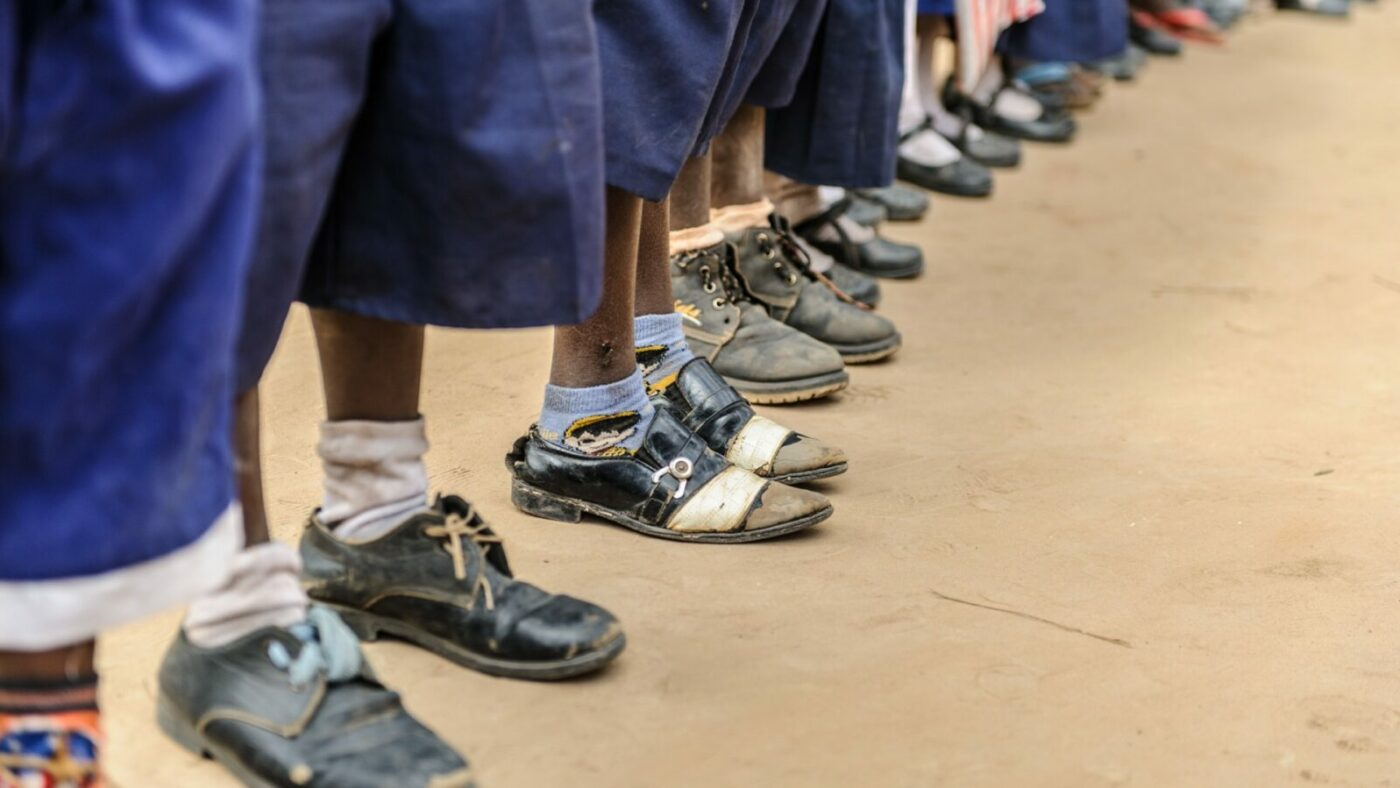 A line of schoolchildren stand in a school playing field. Only their feet and lower legs are shown. All are wearing blue trousers and black shoes.
