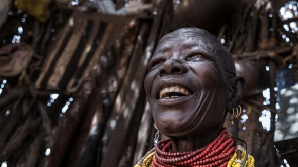 Woman smiles, wearing traditional jewellery, in hut made from branches