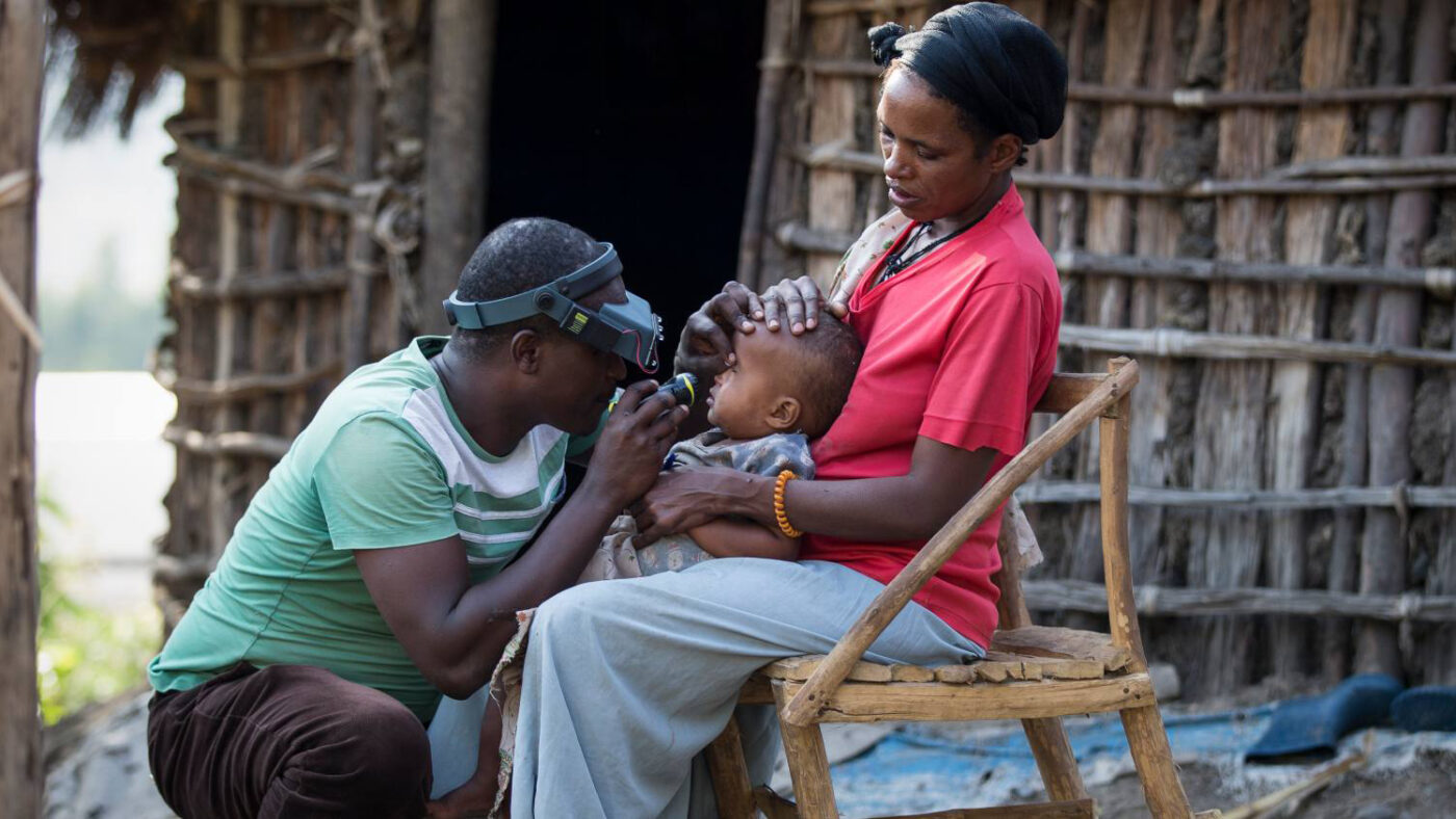 A young child sits on his mother's knee while getting his eyes tested.